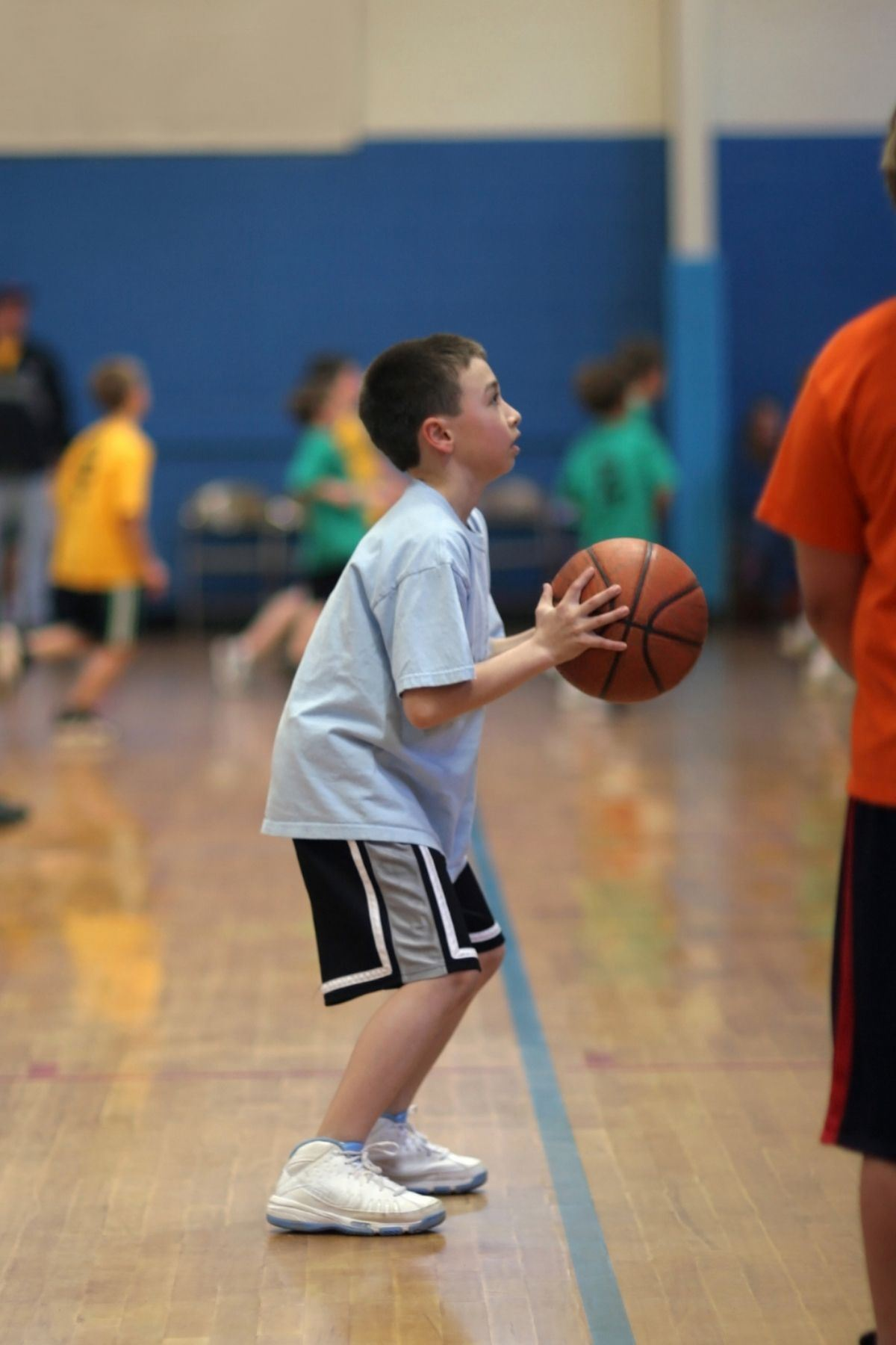 Photo of youth crouching to throw a basketball
