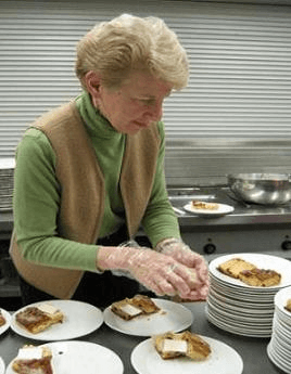 Volunteer serving dinner